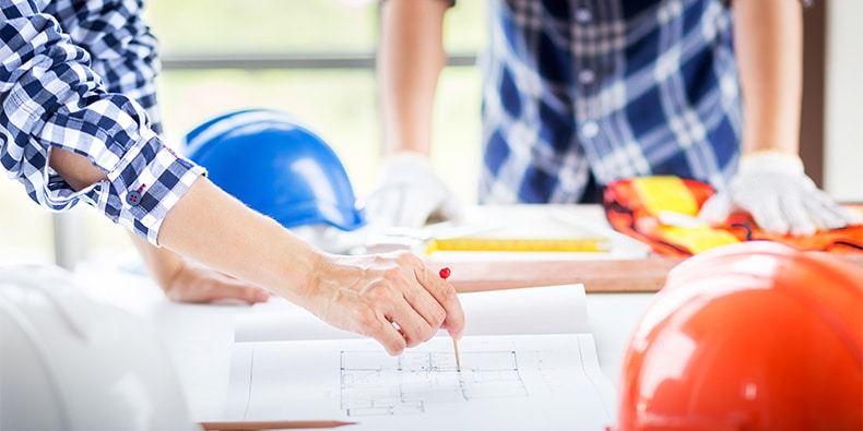 closeup hand of engineer manager point out with red pin point on construction blueprint on working table in construction site with safety helmet in planing meeting