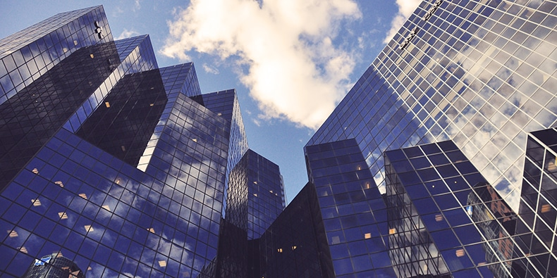 Photo of reflective high-rise office buildings taken from the ground with the sky above