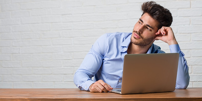 Young business man sitting and working on a laptop looking up, thinking of something fun and having an idea, concept of imagination, happy and excited