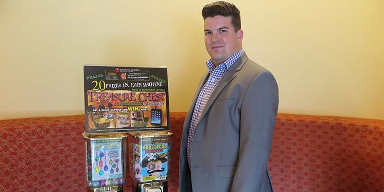 Dan Hein, owner of Happy Days Vending, standing with one of his vending machines