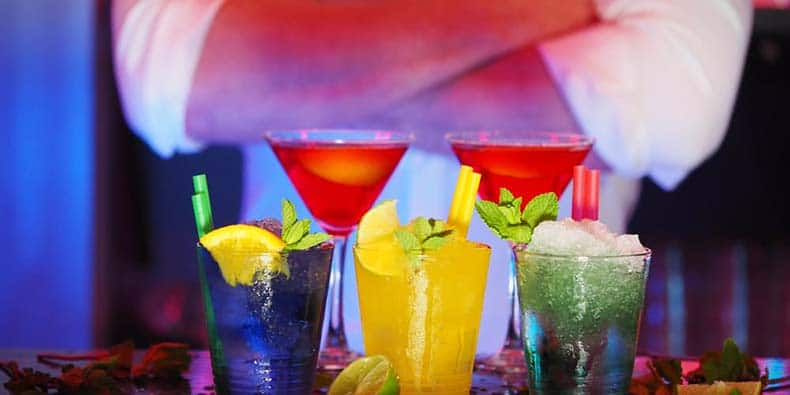 Bartender standing at bar behind several different colourful mixed drinks