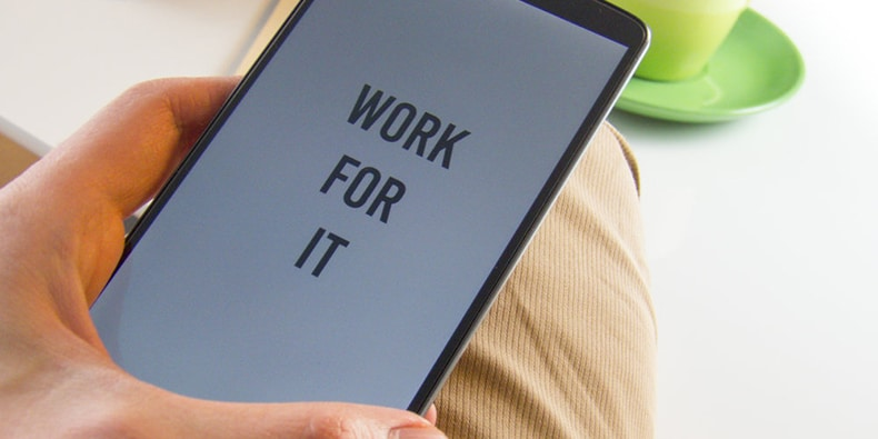 Man holding phone that says Work For It on the screen