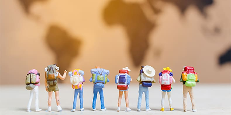 Miniature people travelers walking on world map , Traveling and exploring the world Concept